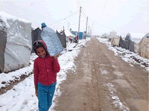 雪が降るイラクの難民キャンプにコートを配る