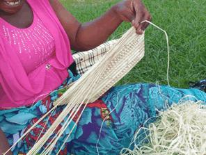 ウガンダの女性に手作りバスケットの技術支援をする